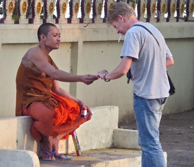 курящий монах в Лаосе